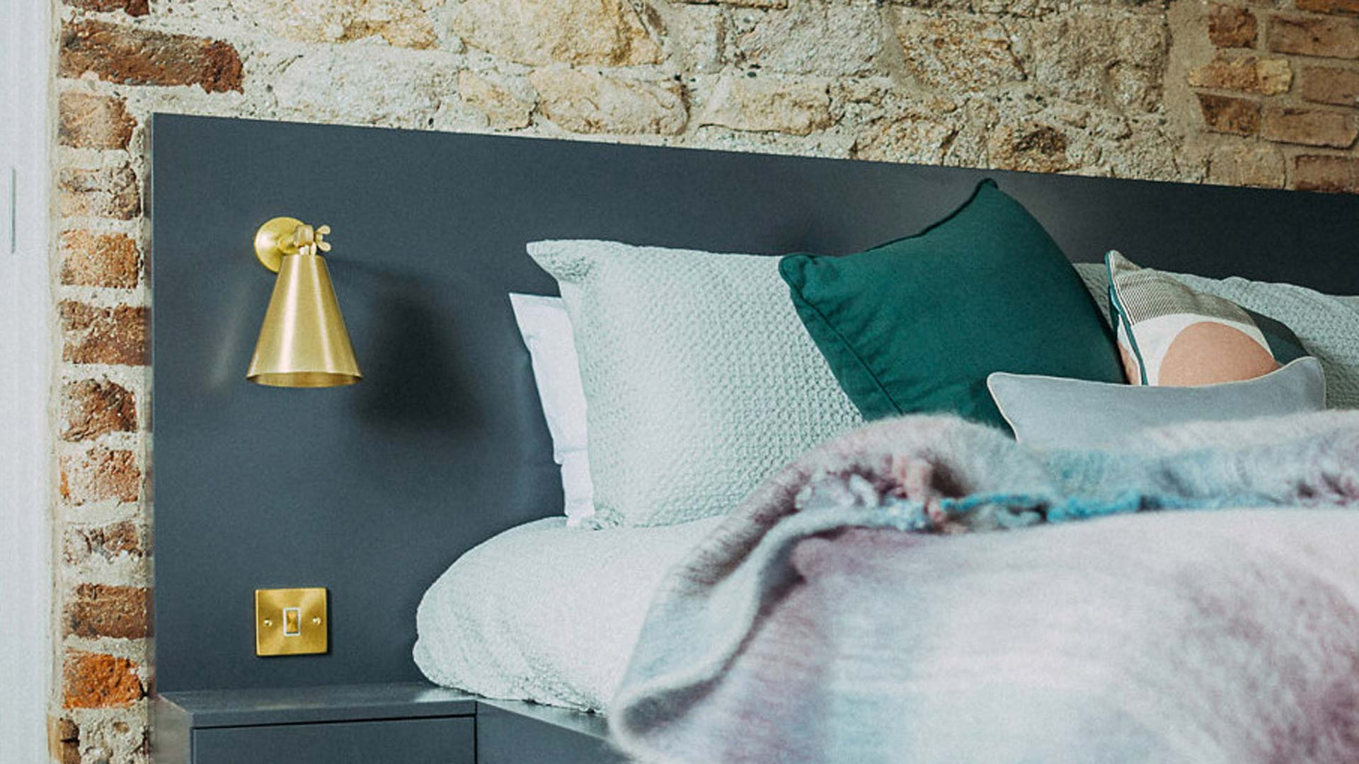 Our Moya bedroom wall lights accent the exposed brick walls at Bolton Park
