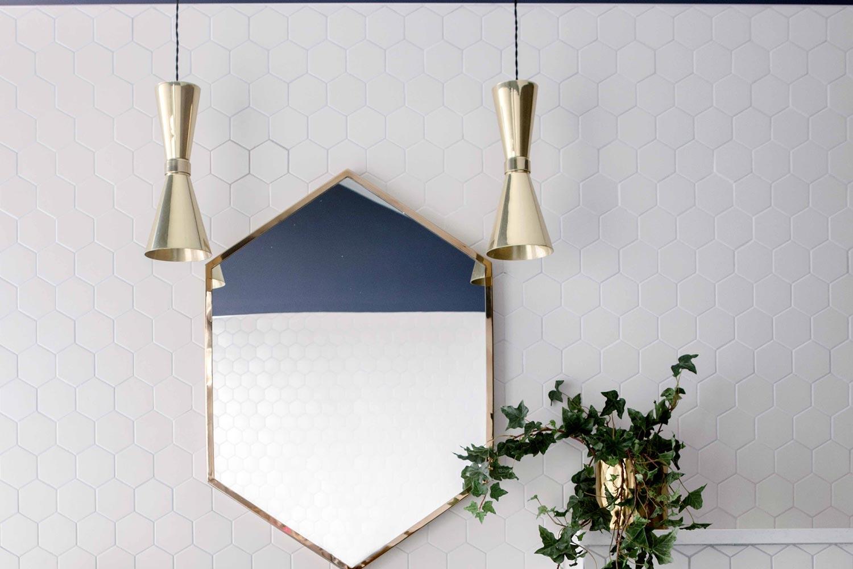 Polished brass Amias pendants add golden glow to this elegant bathroom