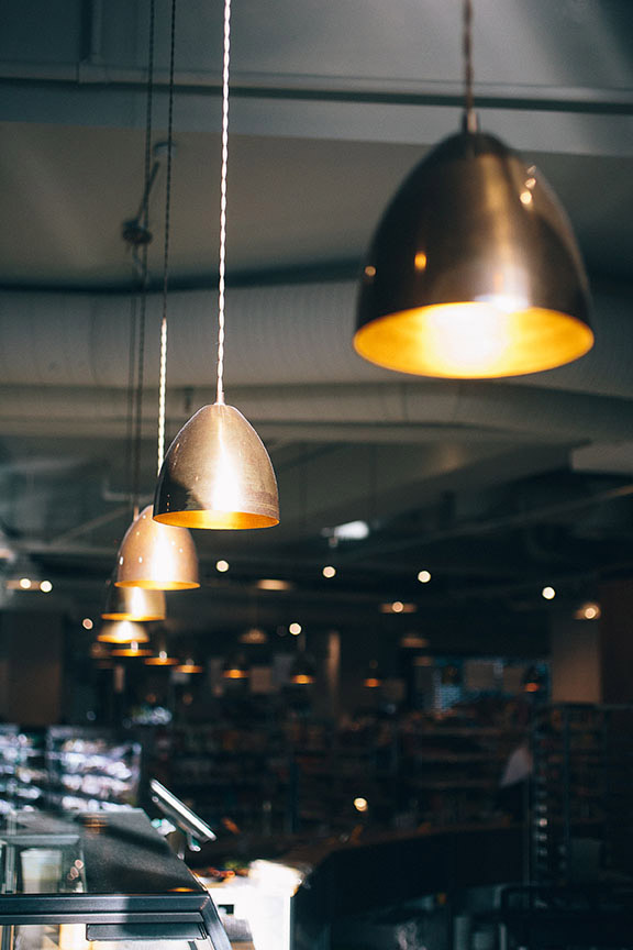 The tasteful Fallon & Byrne features our Skyler Industrial cone pendants